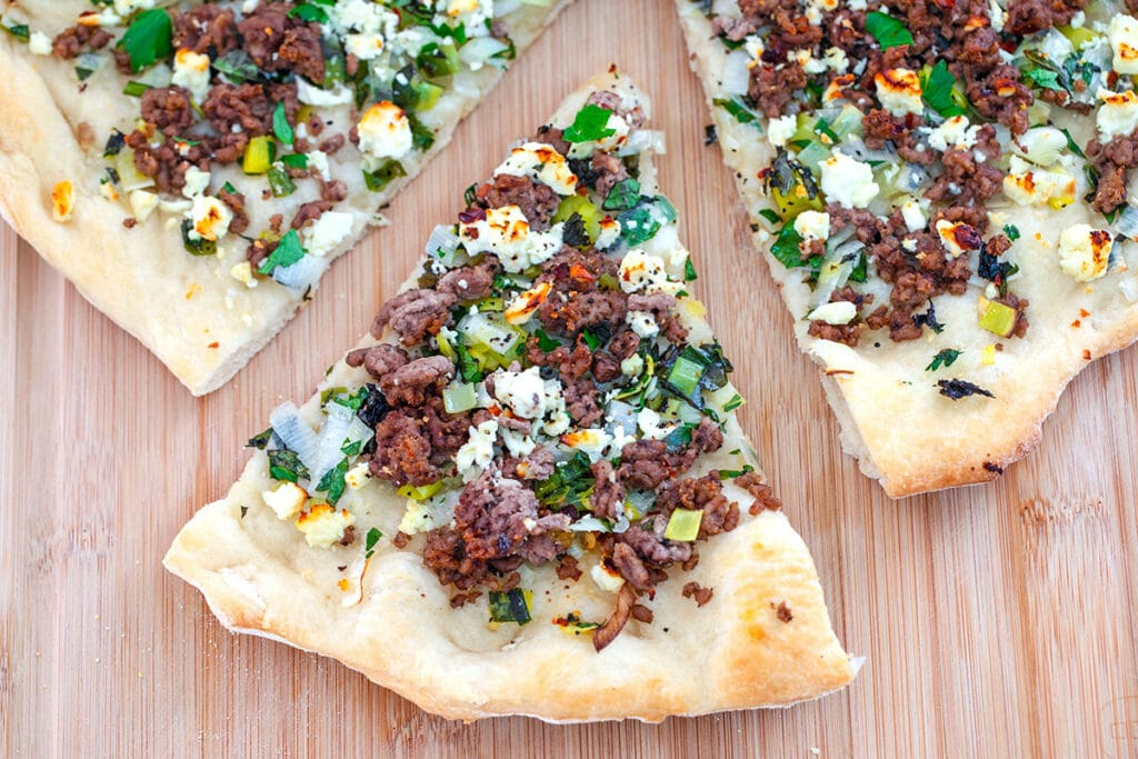 Landscape overhead view of a slice of lamb flatbread with mint and feta pulled out from rest of the pizza on wooden board