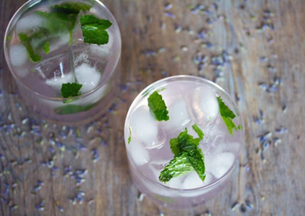 Landscape photo with a bird's eye view of two lavender lemonade mojito cocktails on a wooden surface with dried lavender sprinkled around