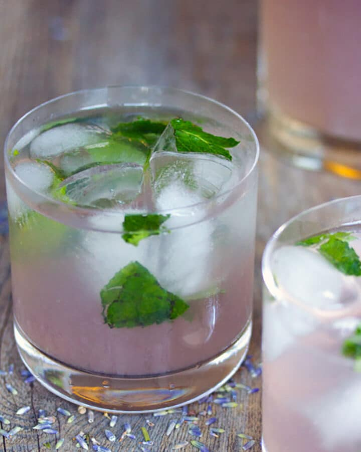Two lavender lemonade mojitos with ice and mint on wooden surface with lavender buds all around
