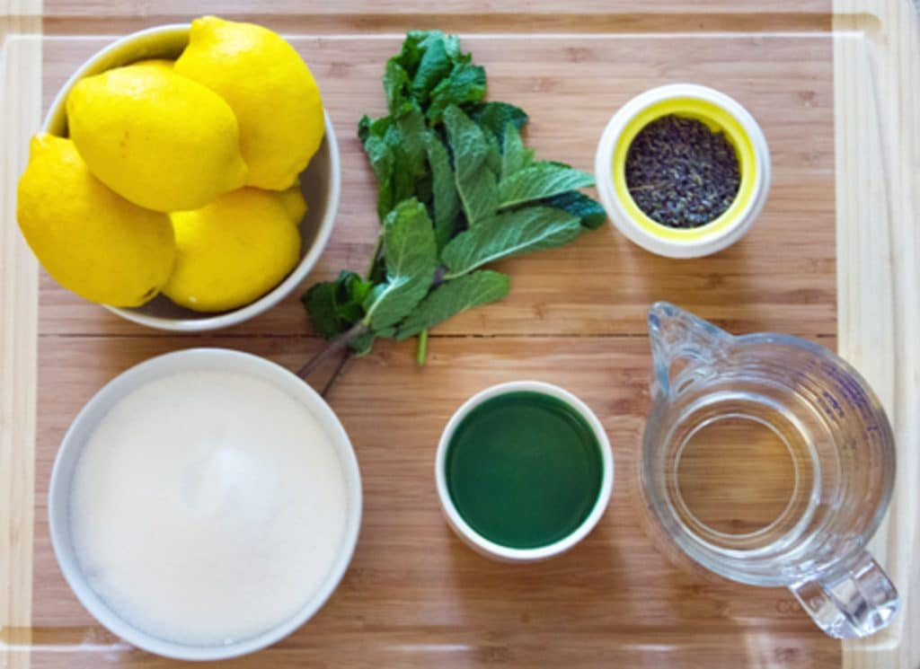 All of the ingredients needed for lavender lemonade mojitos set out: lemons, mint, sugar, water, rum, and dried lavender