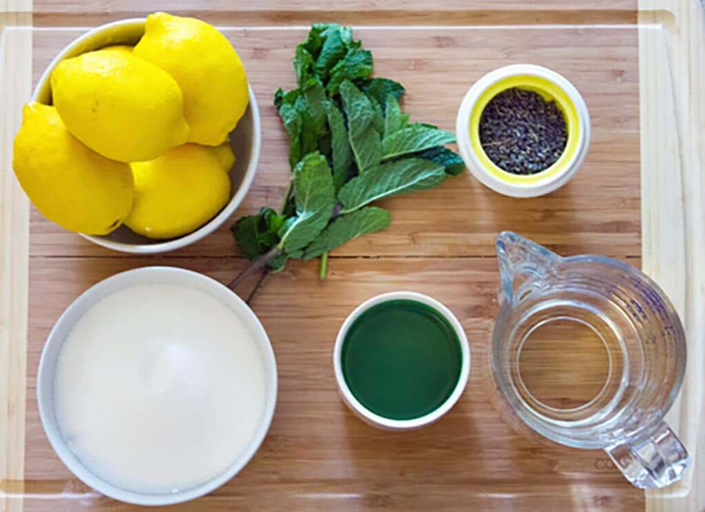 Lemons, mint, sugar, water, rum, and dried lavender all on cutting board