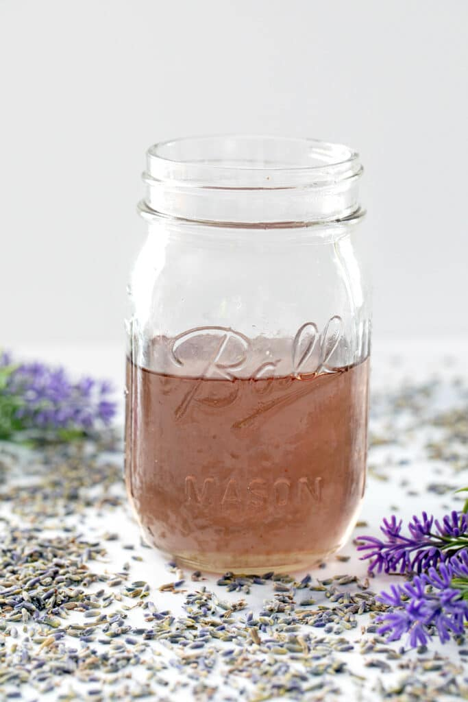 View of a mason jar filled with lavender simple syrup with lavender all around