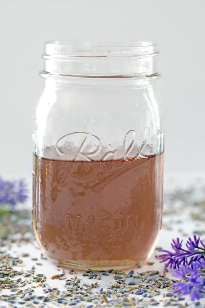 Head-on view of a mason jar filled with lavender simple syrup with lavender all around