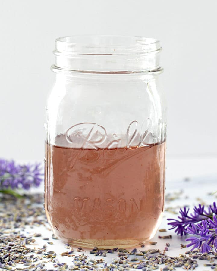 Head-on view of a mason jar of lavender simple syrup with lavender flowers all around