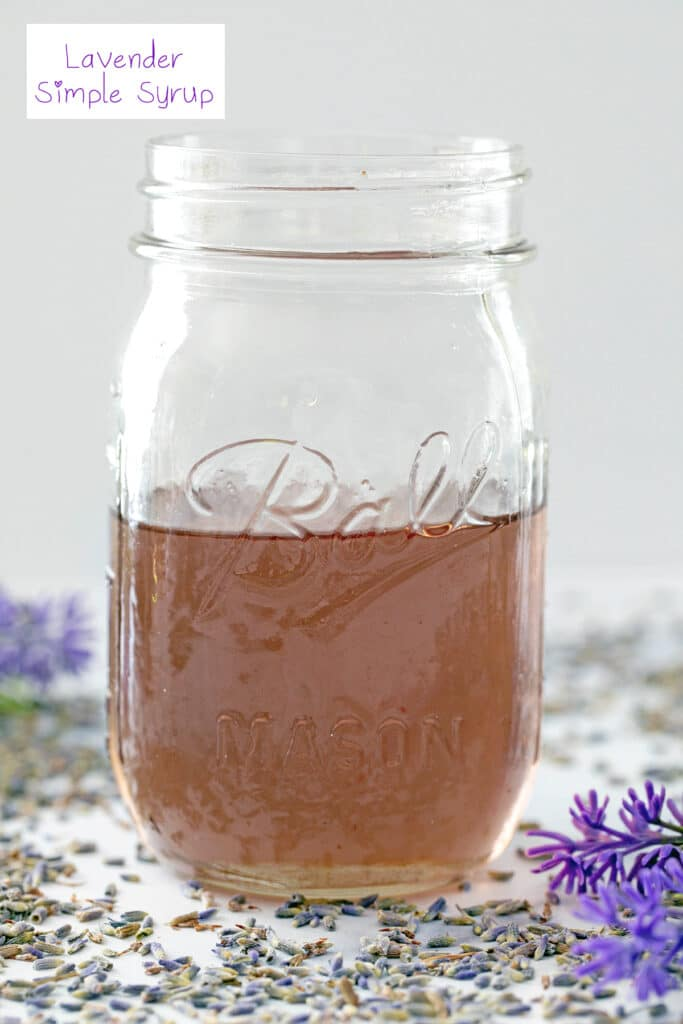 Head-on view of a mason jar filled with lavender simple syrup with lavender all around and recipe title at top