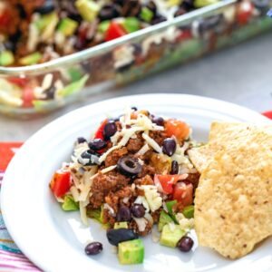 Layered Taco Salad -- Think layered taco salads are just for parties? Think again! This salad features layers of lettuce, beef, tomatoes, avocados, black beans, cheese, and olives and makes for the most delicious dinner | wearenotmartha.com