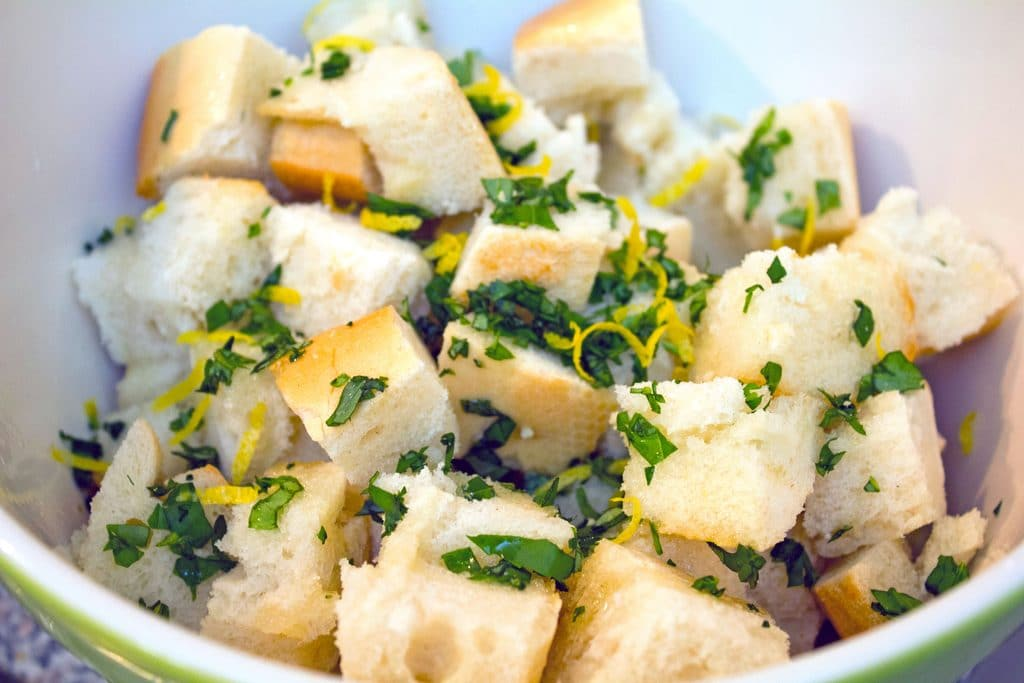 Overhead view of cubed bread in a bowl covered with olive oil, chopped basil, and lemon zest