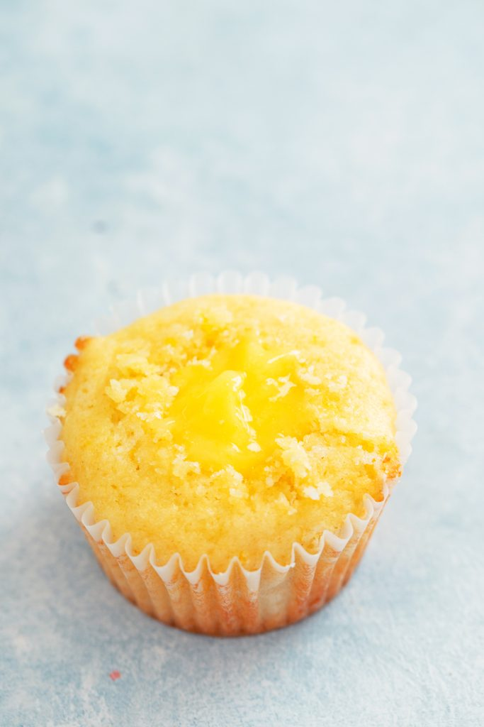 Overhead view of lemon cupcake with core cut out and filled with lemon curd