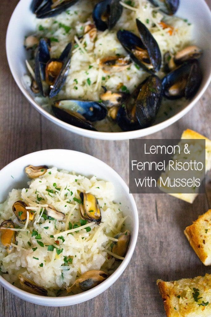 Overhead view of a serving bowl of risotto with mussels (in shells) with a smaller bowl of risotto with mussels (out of shells) in front of it and garlic bread on the side with recipe title on the image