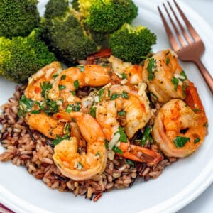 Closeup view of lemon garlic parmesan shrimp over a bed of wild rice with side of broccoli
