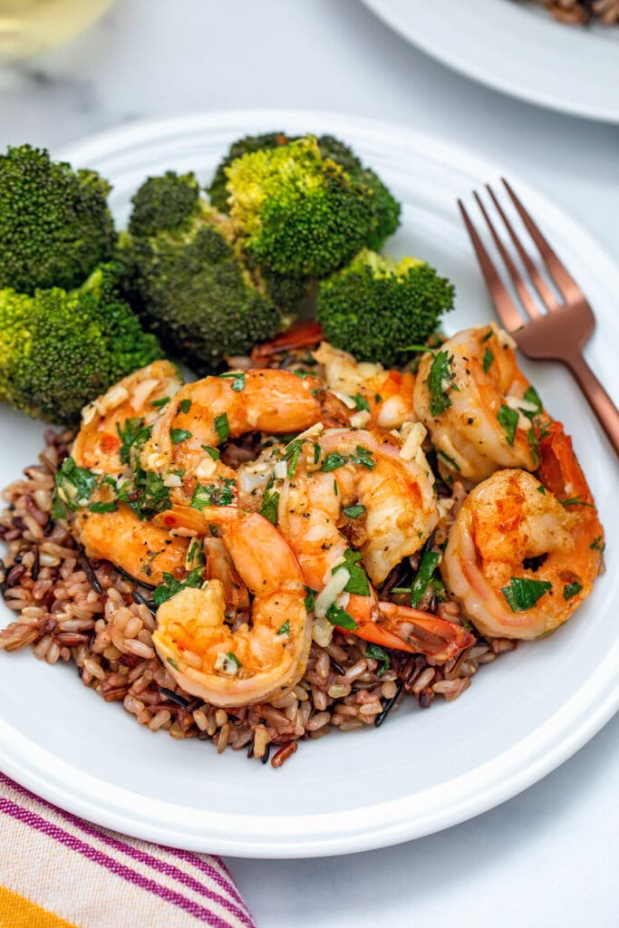 Head-on view of lemon garlic parmesan shrimp over rice with side of broccoli and rose gold fork