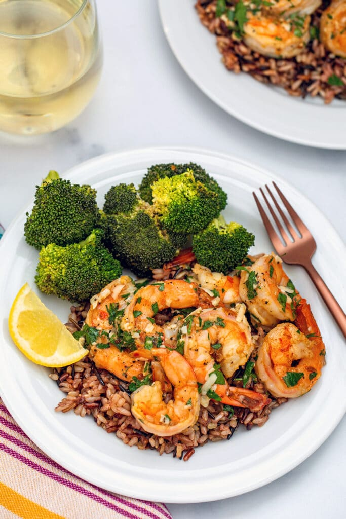 Overhead view of lemon garlic parmesan shrimp on a plate over rice with broccoli, a lemon wedge, and a fork with glass of white wine and second plate in background