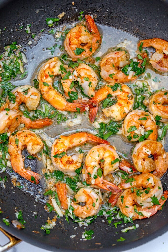 Shrimp cooking in a saute pan with butter, garlic, and parsley