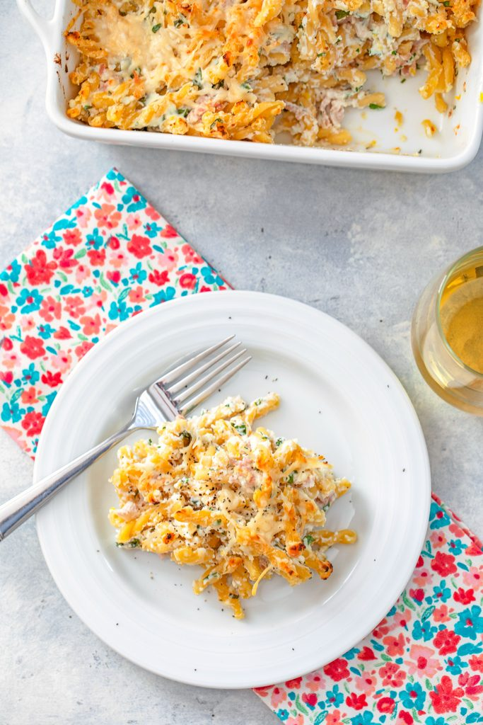 Bird's eye view of serving of lemon ricotta pasta on white plate with fork on flowered towel with casserole dish of baked pasta and glass of white wine in the background