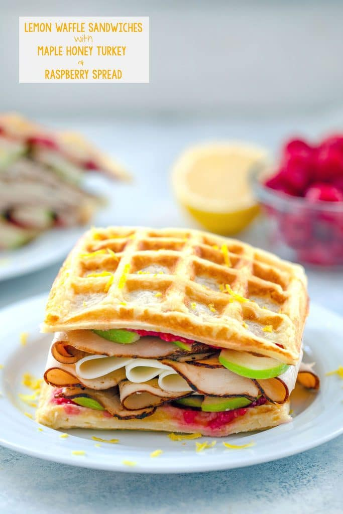 Head-on view of lemon waffle sandwiches loaded with turkey, cheese, raspberry spread, and green apples with raspberries and lemon half in background and recipe title text at top