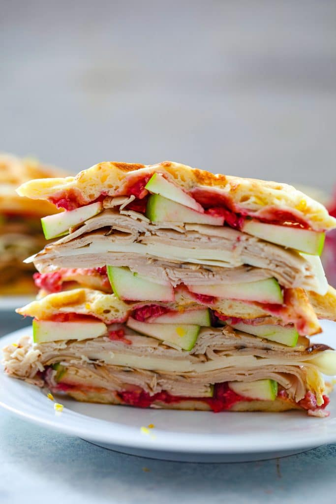 Head-on view of lemon waffle sandwiches sliced in half and stacked on top of each other and filled with turkey, cheese, green apple, and raspberry spread