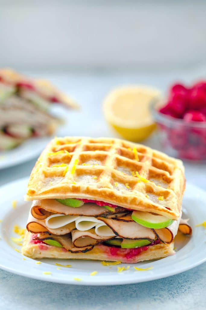 Head-on view of lemon waffle sandwiches loaded with turkey, cheese, raspberry spread, and green apples with raspberries and lemon half in background