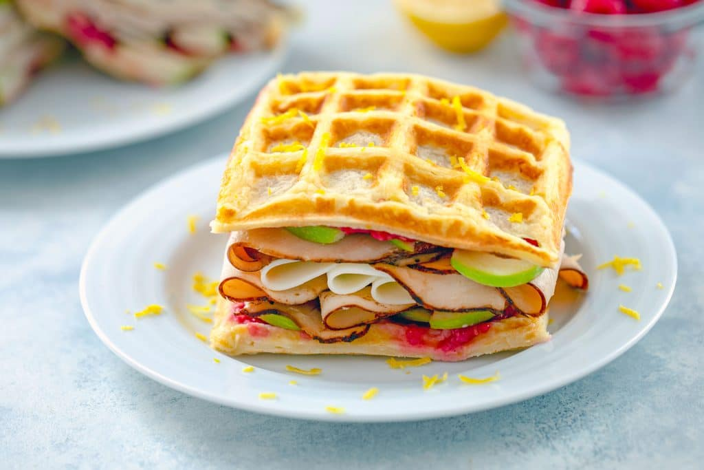 Landscape view of lemon waffle sandwich on a white plate loaded with turkey, cheese, green apples, and raspberry spread with lemon zest sprinkled on top