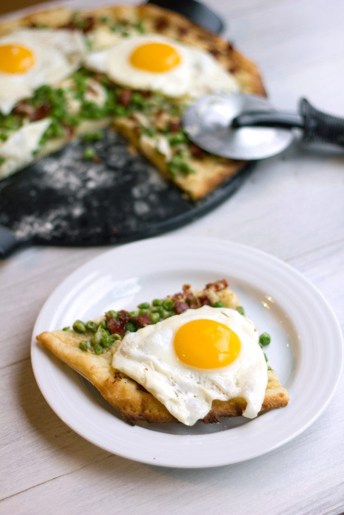 Head-on view of slice of lemon parmesan spring flatbread with ricotta, peas, capicola, and eggs on a white plate with rest of pizza and pizza cutter in background