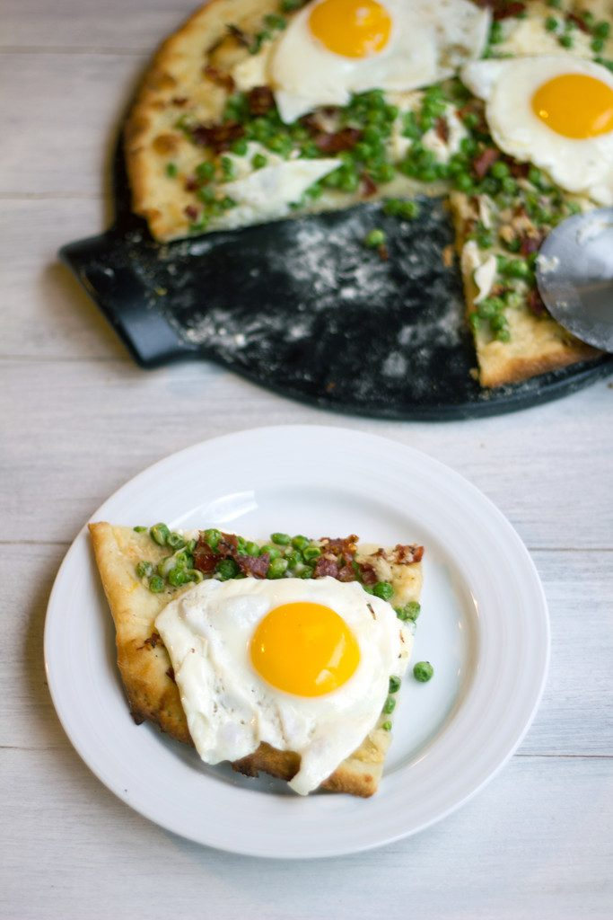 Bird's eye view of slice of lemon parmesan spring flatbread with eggs on top on a small white plate with remaining pizza in pan in background
