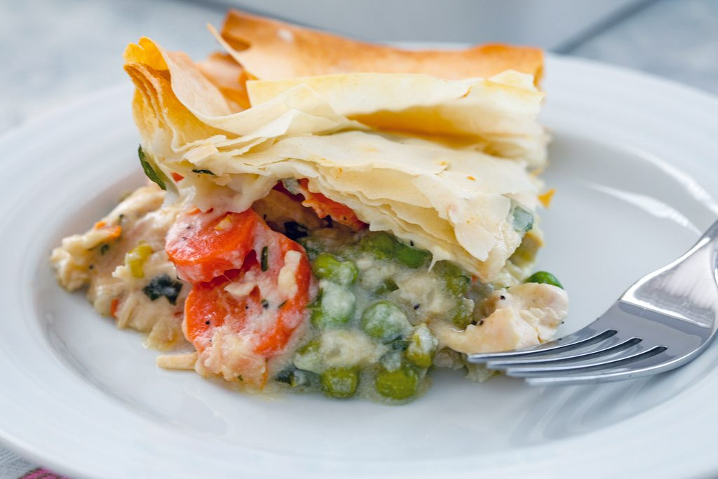 Landscape close-up head-on view of lighter chicken pot pie with peas and carrots on a white plate with a fork