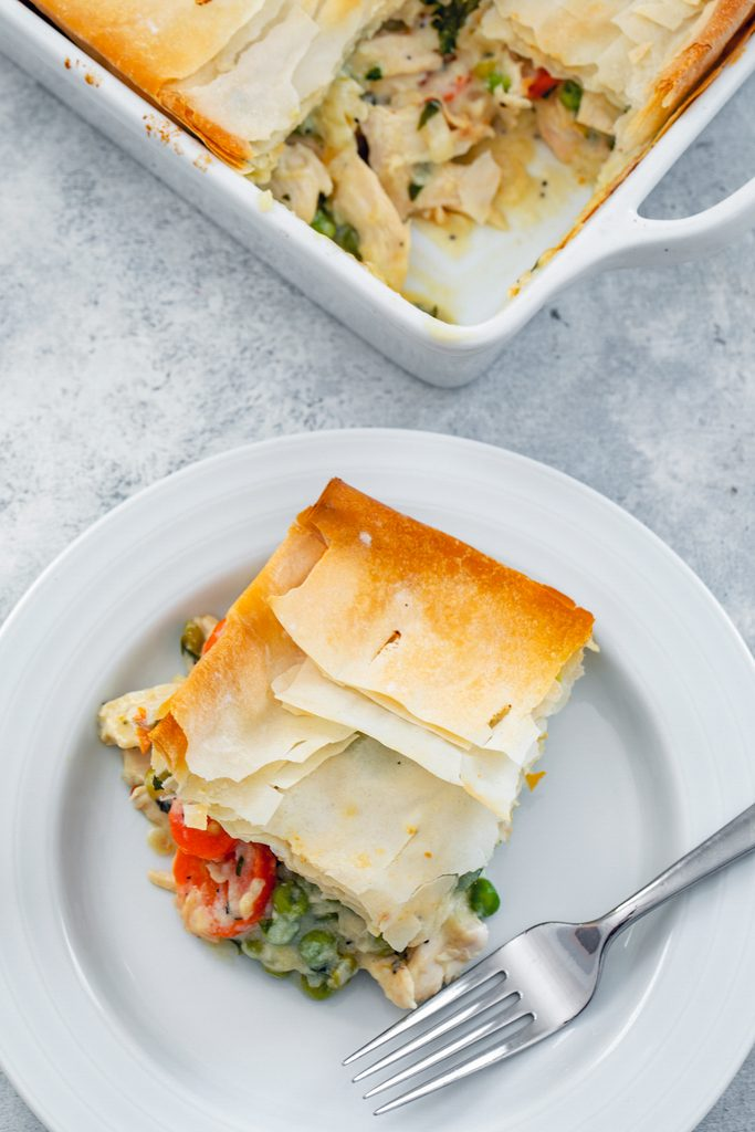 Bird's eye view of lighter chicken pot pie serving on a white plate with a fork with baking dish in the background