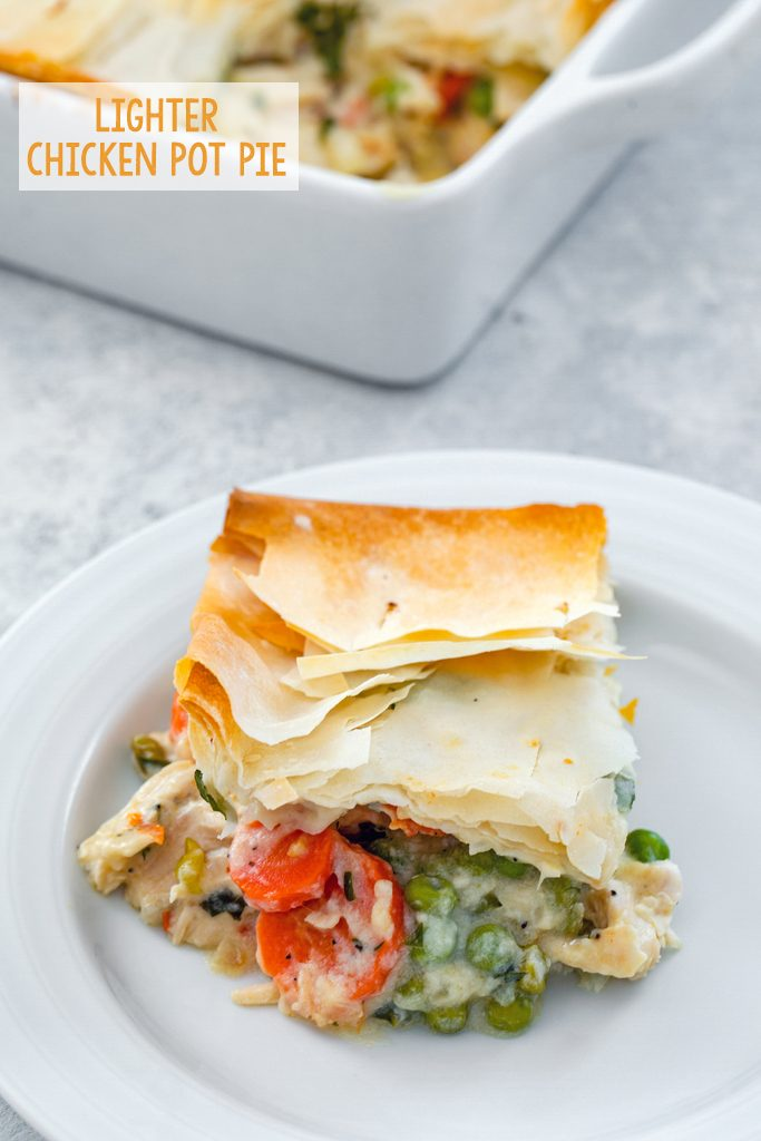 Overhead view of a serving of lighter chicken pot pie with peas and carrots on a white plate with the baking dish in the background and recipe title at top