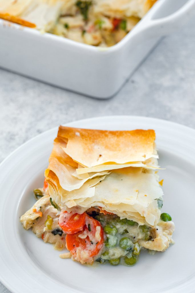 Overhead view of a serving of lighter chicken pot pie with peas and carrots on a white plate with the baking dish in the background