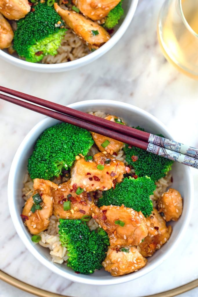 Overhead view of white bowl of sesame chicken and broccoli over brown rice with chopsticks on a marble surface with second bowl and glass of white wine in background