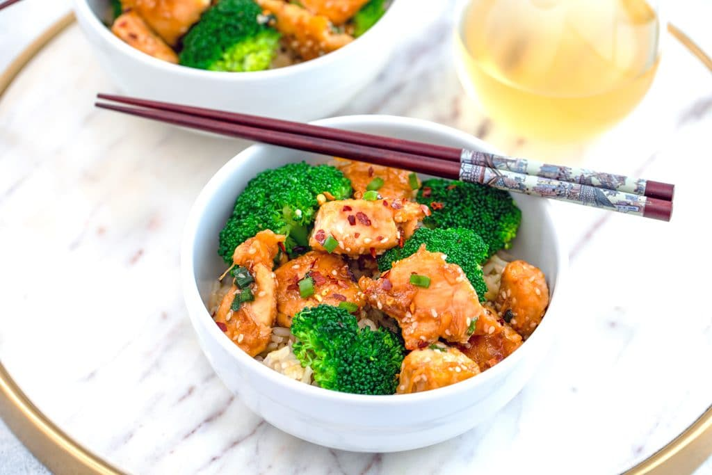 Landscape view of white bowl of sesame chicken and broccoli over rice with chopsticks over top on marble surface with glass of white wine in background