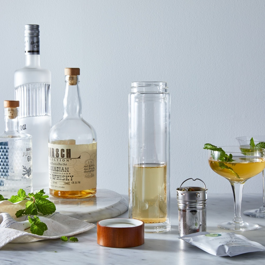 Head-on view of liquor infusion set with various bottles of liquor, glasses of cocktails, and herbs