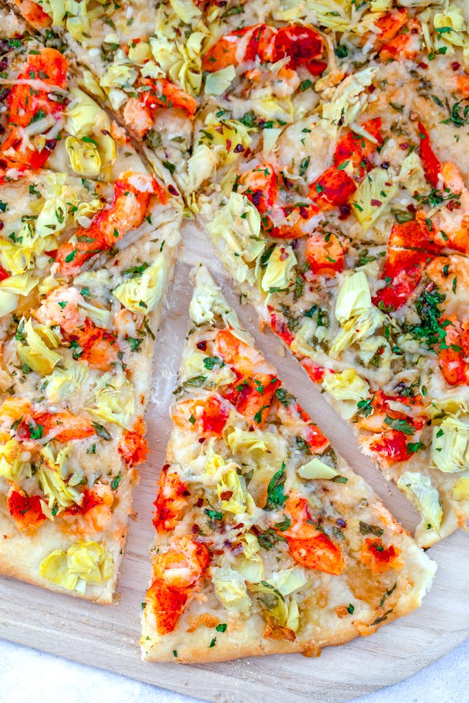 Overhead view of a lobster flatbread pizza with artichokes with a slice pulled out