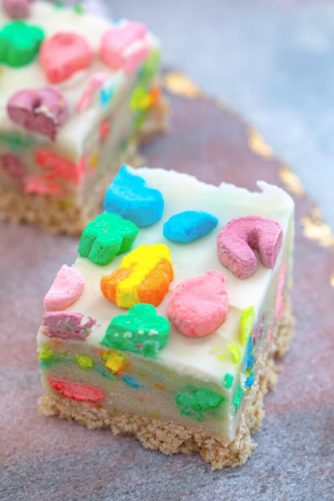 Closeup overhead view of a Lucky Charms cookie dough bar with buttercream frosting top with marshmallows