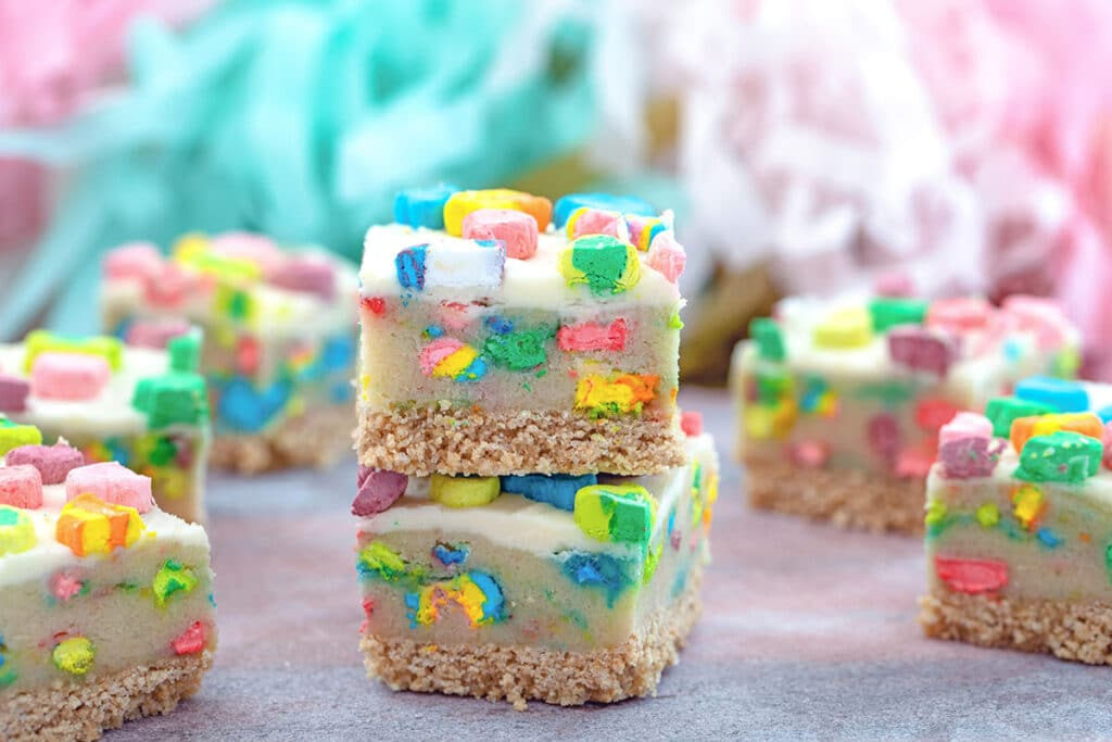 Landscape head-on view of two Lucky Charms cookie dough bars stacked on each other with lots more bars all around