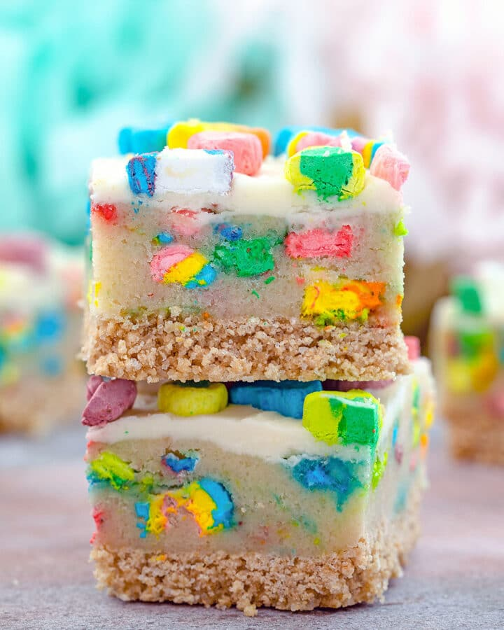 Head-on view of two Lucky Charms cookie dough bars stacked on each other with more bars in the background