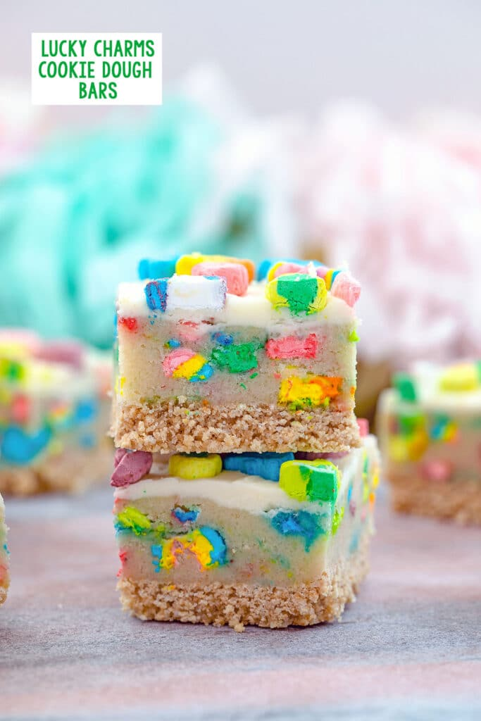 Head-on closeup view of two Lucky Charms cookie dough bars with cereal crust and buttercream frosting with more bars in the background and recipe title at top