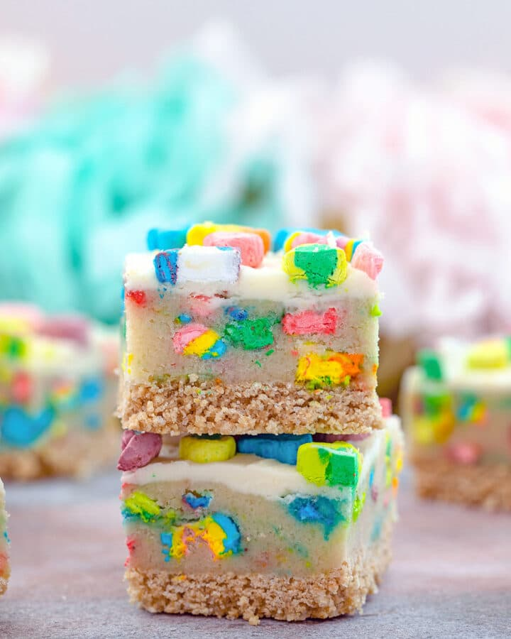Two Lucky Charms cookie dough bars stacked on top of each other with more bars in background