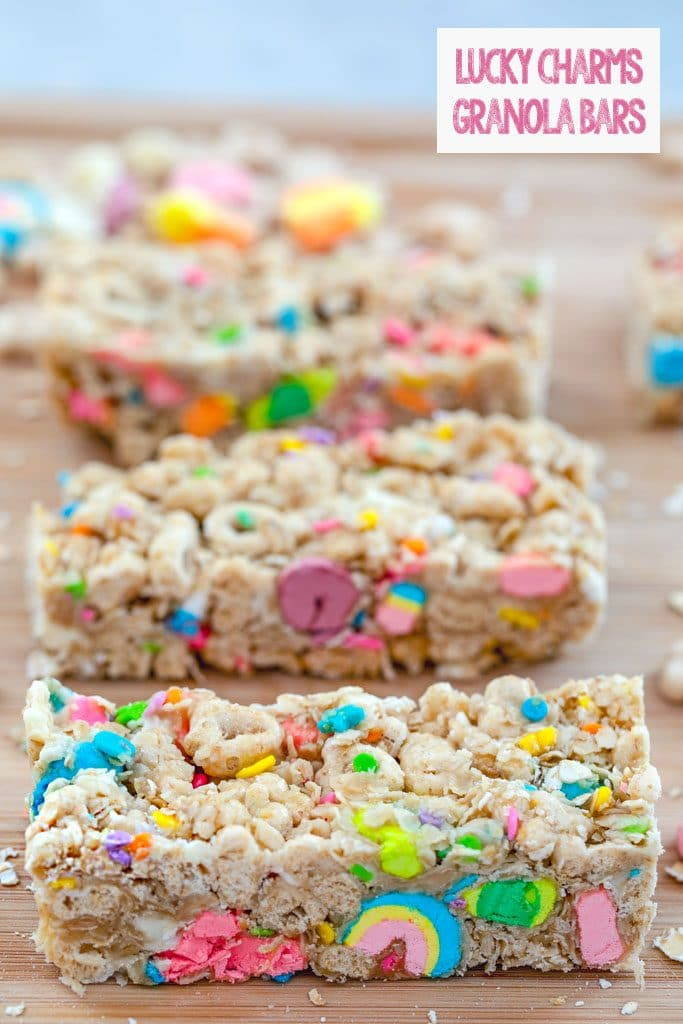 Overhead view of Lucky Charms granola bars lined up on a cutting board with recipe title at top