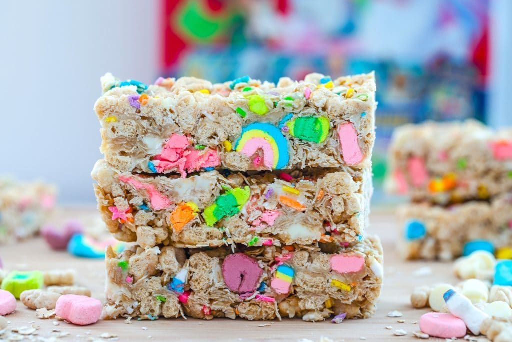 Landscape close-up view of three Lucky Charms granola bars stacked on each other on a wooden board with oats, cereal, and white chocolate chips scattered around and cereal box in background
