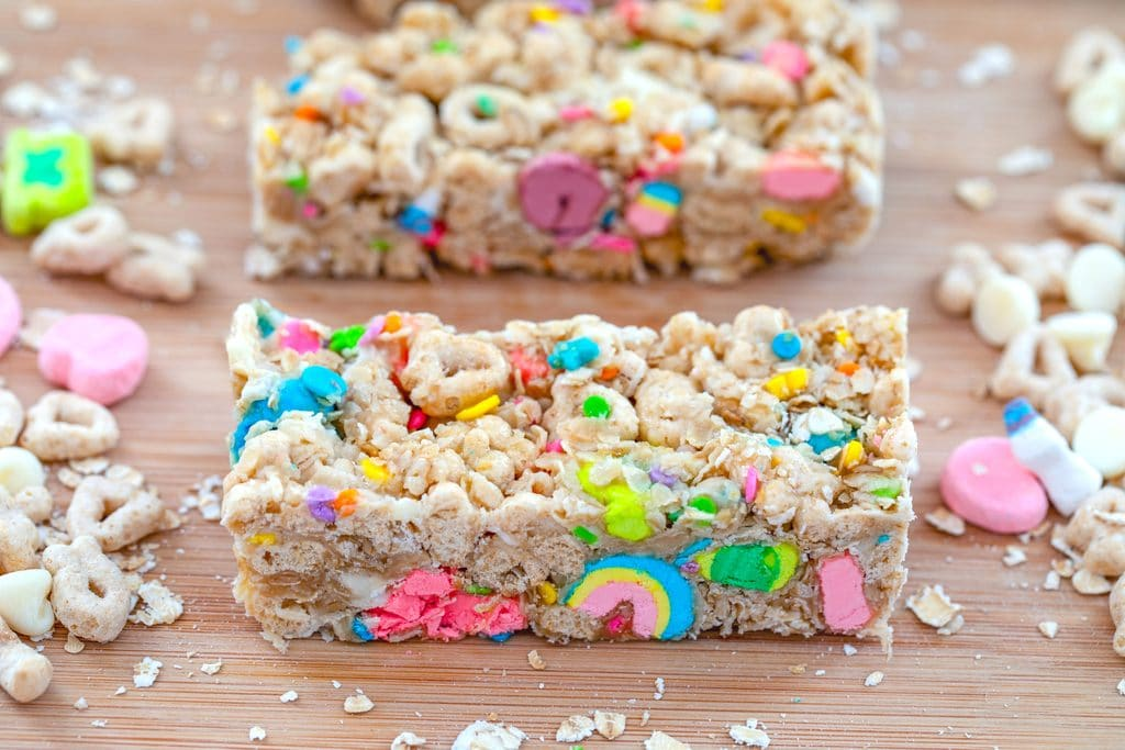 Landscape close-up view of a Lucky Charms granola bar on a wooden board surrounded by Lucky Charms cereal and oats