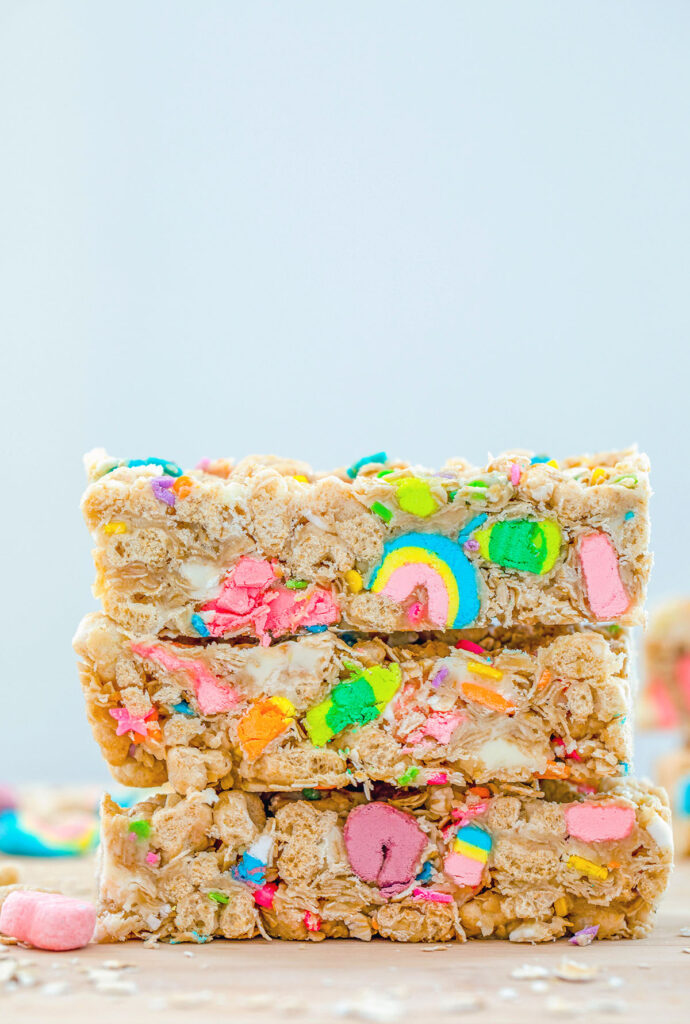 Head-on view of three Lucky Charms granola bars stacked on each other with extra oats and marshmallows in the background