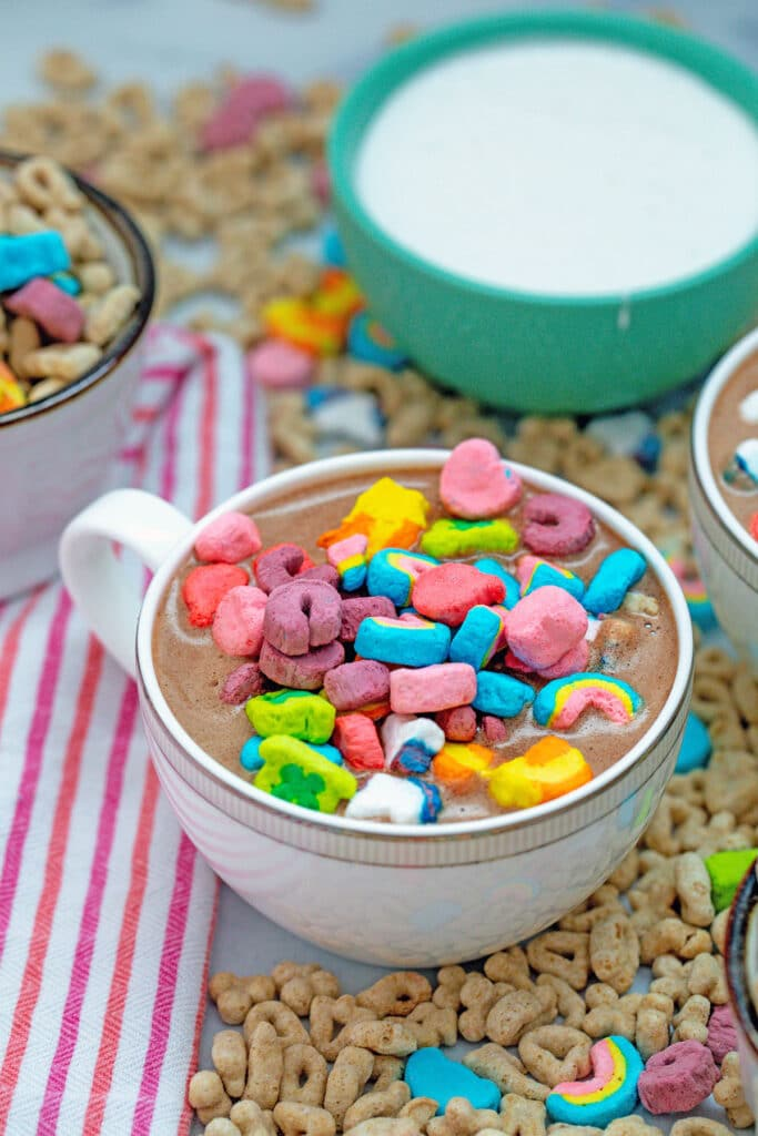 Head-on view of a small mug of Lucky Charms hot chocolate topped with cereal marshmallows with marshmallow fluff in background and cereal all around