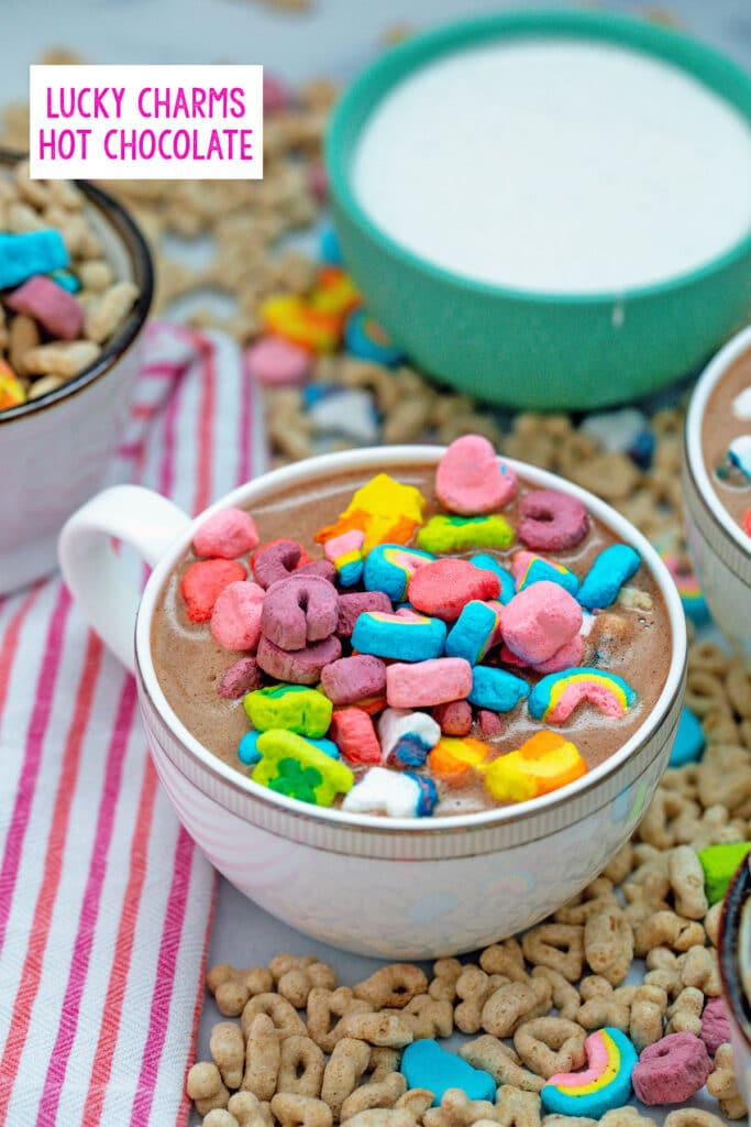 Head-on view of a small mug of Lucky Charms hot chocolate topped with cereal marshmallows with marshmallow fluff in background and cereal all around with recipe title at top