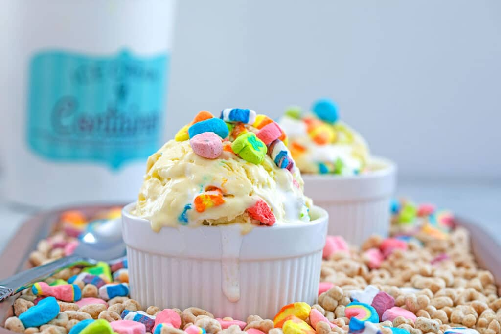 Landscape view of white bowl of Lucky Charms ice cream on a bed of cereal with second bowl, quart container, and spoon in the background