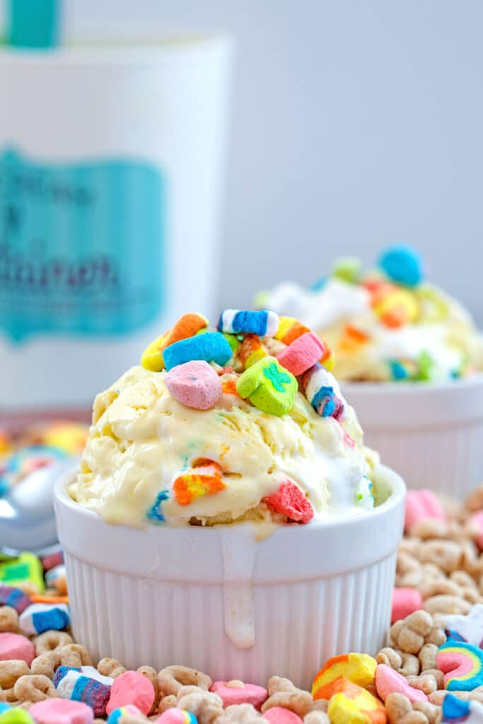 Head-on view of Lucky Charms ice cream in a white bowl topped with marshmallows on a bed of cereal with quart container and second bowl in the background