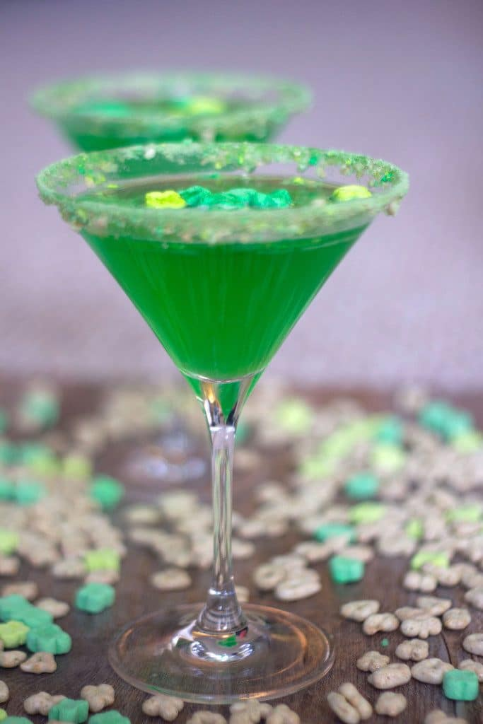 Head-on view of green Lucky Charms Martini with Lucky Charms cereal and second martini in background