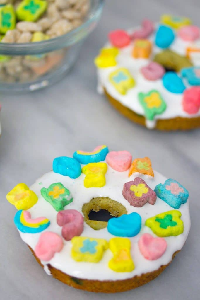 Overhead view of Lucky Charms doughnuts with marshmallow icing and marshmallows on a marble surface with bowl of Lucky Charms in the background