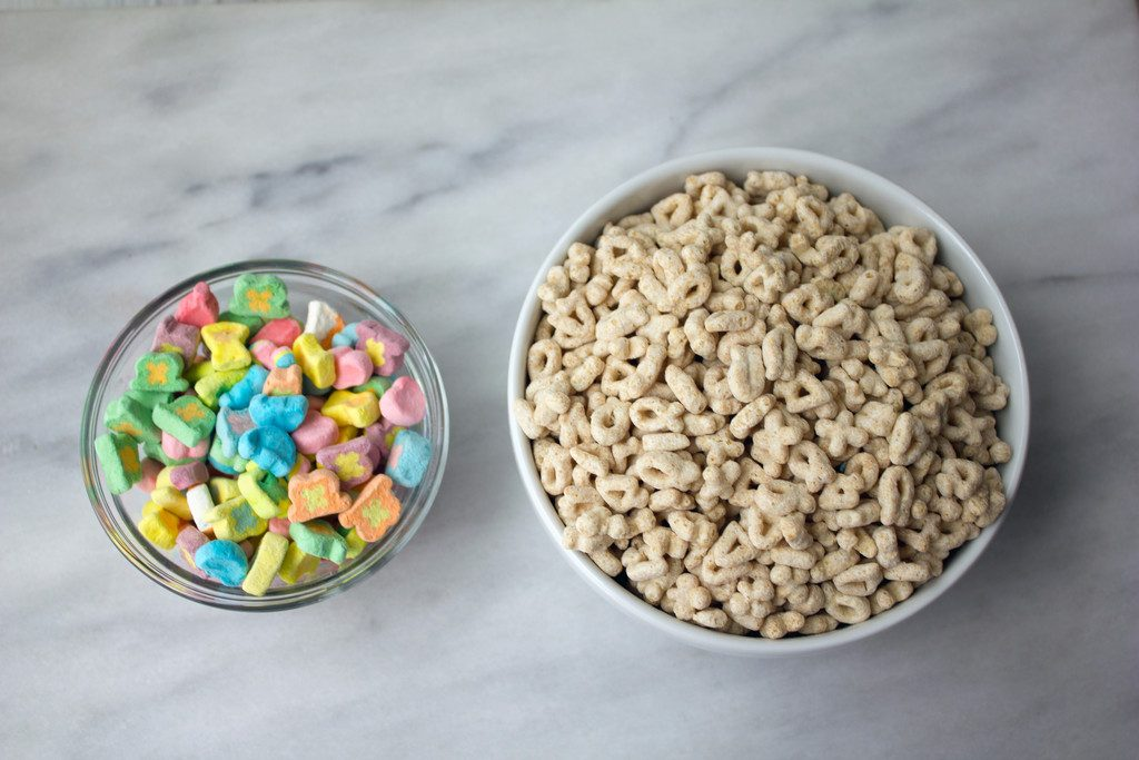 Overhead view of a bowl of Lucky Charms marshmallows and a bowl of Lucky Charms cereal with the marshmallows removed