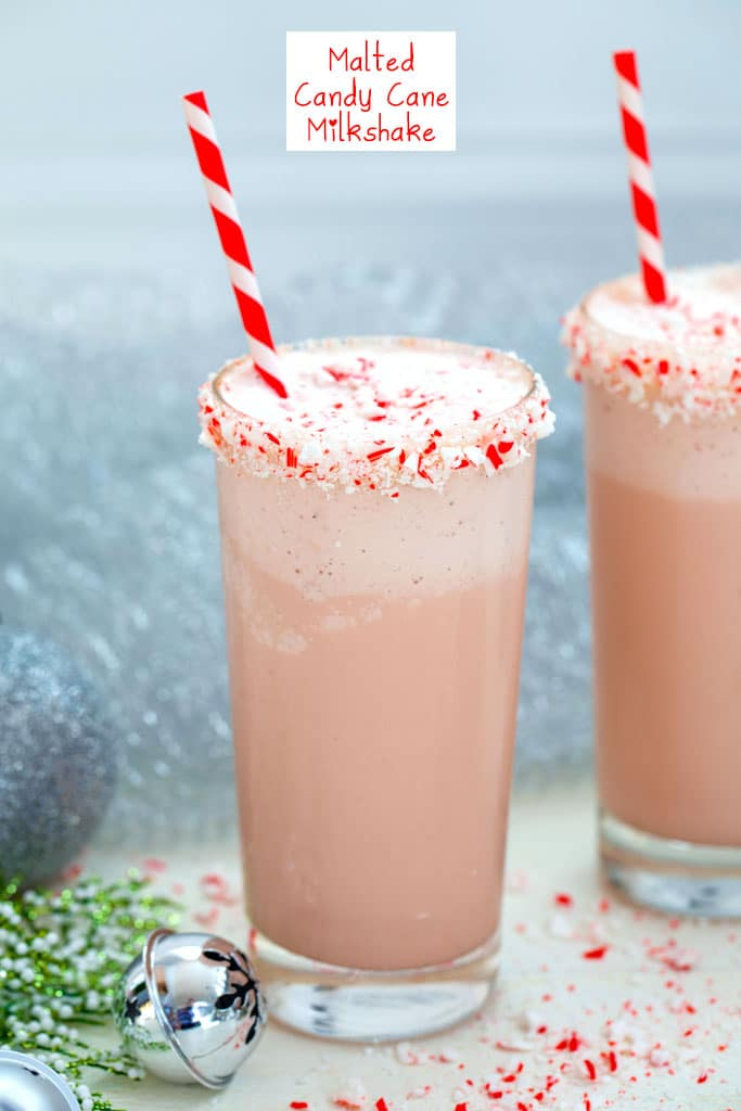 Head-on view of a malted candy cane milkshake with crushed candy cane rim with red and white striped straw with second milkshake, silver bells, and holly in background with recipe title at top