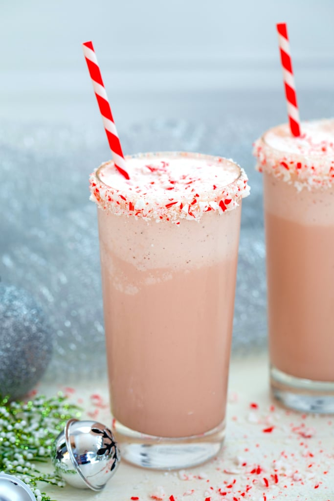 Head-on view of a malted candy cane milkshake with crushed candy cane rim with red and white striped straw with second milkshake, silver bells, and holly in background